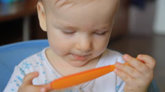 Infant spits out the nipple and played with a plastic spoon Stock Footage