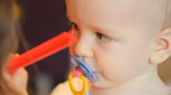 Baby with a pacifier in his mouth at the hands of her mother Stock Footage