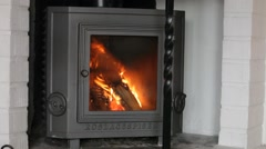 Stock Video Footage of Wooden logs are burning in a cassette built into an open-hearth fireplace