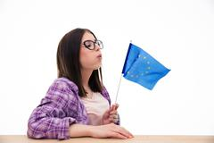 Young woman blowing on the europian flag - stock photo