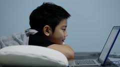 Asian cute boy watching and talking on laptop computer. Arkistovideo