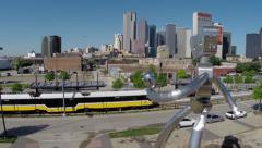 Dallas Skyline aerial w/ large sculpture and Dart train at station NICE Stock Footage