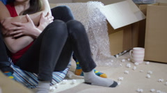 4K Happy affectionate young couple sitting amongst cardboard boxes in new home - stock footage