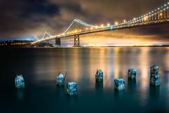 Pier pilings and the San Francisco - Oakland Bay Bridge at night, in San Fran Kuvituskuvat