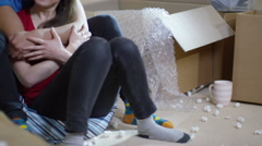 4K Happy affectionate young couple sitting amongst cardboard boxes in new home Stock Footage