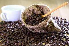 Coffee beans in bag with wooden spoon and cup background. Stock Photos