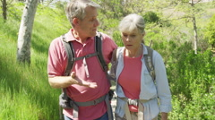 Senior couple using smartphone for directions outdoors Stock Footage