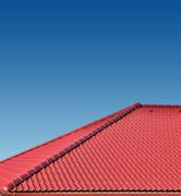 Roof with red tiles on a background of blue sky, new roof Stock Photos