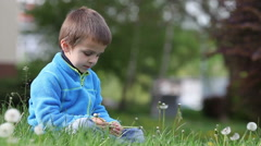 Happy cute caucasian boys, brother, blowing dandelion outdoors in spring park Stock Footage