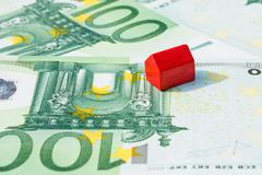 Concept house sell, foreclosure, debt, bill, mortgage on 100 euro banknotes.  Stock Photos