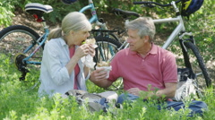 Senior couple eating lunch after biking on trail Stock Footage