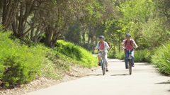Happy active senior couple riding bikes on trail - stock footage