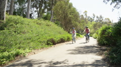 Active senior couple riding bikes outdoors on trail - stock footage