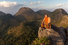 Buddhist master monk meditating in mountains Stock Photos