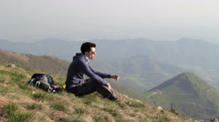 Young man takes a break in the mountains, with views overlooking the plains Stock Footage