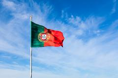 Portugal flag waving on the wind over a cloudy blue sky Stock Photos