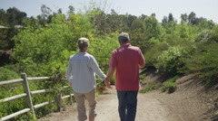 Senior married couple walking on trail together Stock Footage