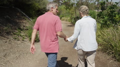 Happy senior couple walking on trail Stock Footage