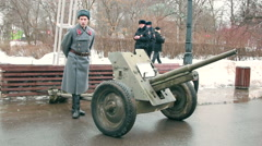 Soldier wearing old soviet military uniform, standing next to artillery gun Stock Footage