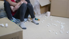 4K Happy young couple sitting amongst cardboard boxes with key to new home - stock footage