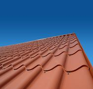 new roof with orange sheet metal and background of blue sky - stock photo