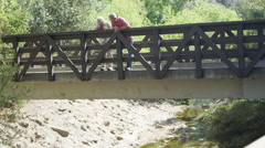 Stock Video Footage of Mature couple on bridge looking down