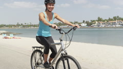 Young healthy woman riding bike along river Stock Footage