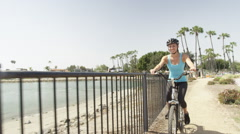 Young woman riding bike along river Stock Footage