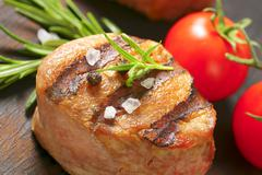 Grilled pork medallion on wood - stock photo
