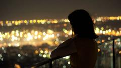 Young  pensive woman looking at cityscape in the evening lights HD Stock Footage