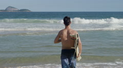 Stock Video Footage of Man with surfboard running towards sea