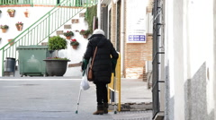 Advanced age woman walking down a street with crutch - stock footage