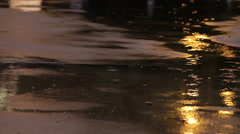 Rain drops on pavement at night - stock footage