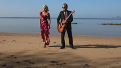 Girl in red clasps to  guitarist's breast on beach at dawn Stock Footage