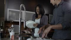 Young attractive couple doing dishes in a modern kitchen - Condo Living Stock Footage