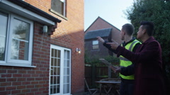 4K Young man outside his home getting planning advice from builder or architect - stock footage