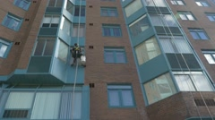 Window washer cleans condo window Stock Footage