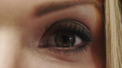 Beautiful woman's eye close up - opening in surprise - stock footage