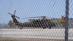 Military black Hawk helicopter behind fence 2 Stock Footage