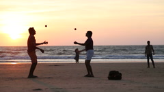 Two men juggling on a sandy beach at sunset. Stock Footage