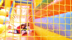 Two girls sliding on inflatable rubber castle playground Stock Footage