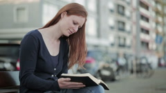 Female Believer Reads the Bible in a City - stock footage