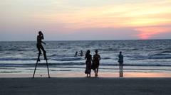 Man dancing on crutches on beach at sunset, with people watching. - stock footage