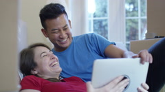 4K Happy young couple with computer tablet, lying on floor in new home - stock footage
