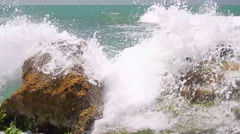 Turquoise rolling wave slamming on the rocks . - stock footage