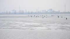 Fishermen angling on ice on background of electric power station Stock Footage
