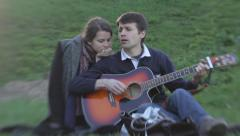 the guy sings and plays guitar for the girl in the Park. Romance, Dating, love - stock footage