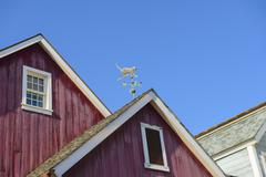 Weather vane on a roof Stock Photos