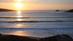 Sunset in Cornwall with surfers still surfing in Crantock  Stock Footage