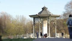 People walk near a beautiful gazebo in a Park in spring Stock Footage